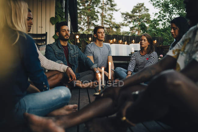 Male and female friends sitting with eyes closed in balcony during group session — Stock Photo