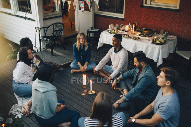 High angle view of male and female friends sitting with eyes closed around lit candles in balcony during group therapy s — стокове фото
