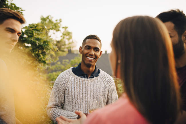 Multi-ethnic friends talking while standing in yard during social gathering — Photo de stock