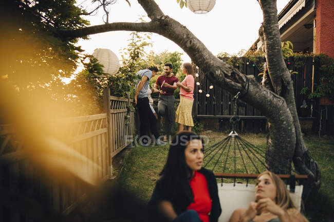 Male and female friends spending leisure time in yard during social gathering — Stock Photo