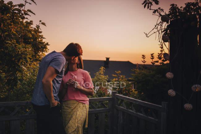 Couple embrasser tandis que debout au balcon pendant le coucher du soleil — Photo de stock