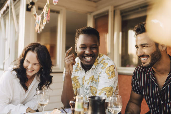 Cheerful friends having fun at dining table during dinner party — Stock Photo