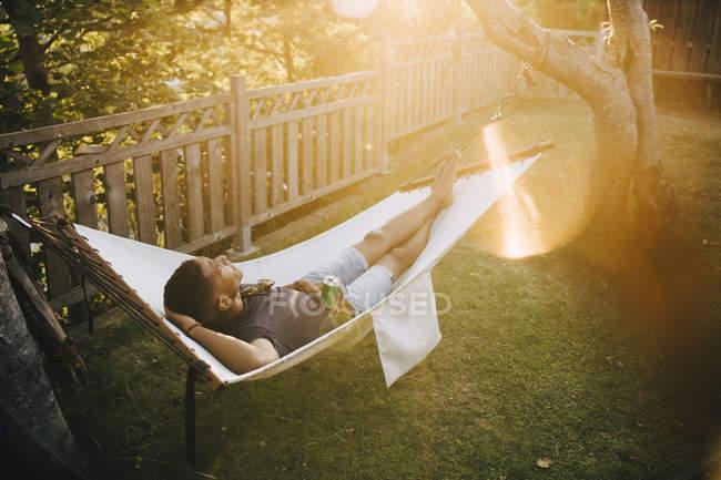 Blick aus der Vogelperspektive auf einen jungen Mann mit Getränken, der auf einer Hängematte im Hinterhof liegt — Stockfoto