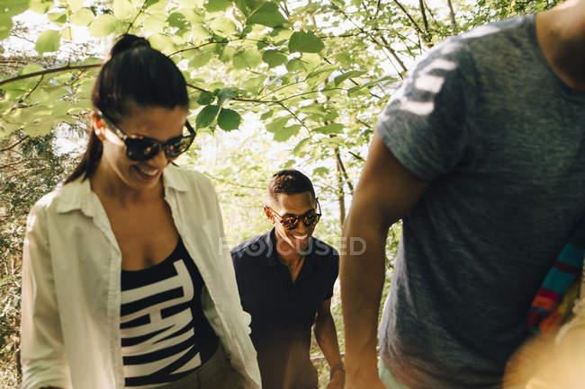 Улыбающиеся мужские и женские друзья, гуляющие в лесу летом — стоковое фото