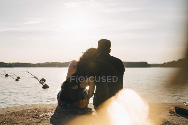 Rear view of romantic couple sitting on jetty against lake during summer — Stock Photo