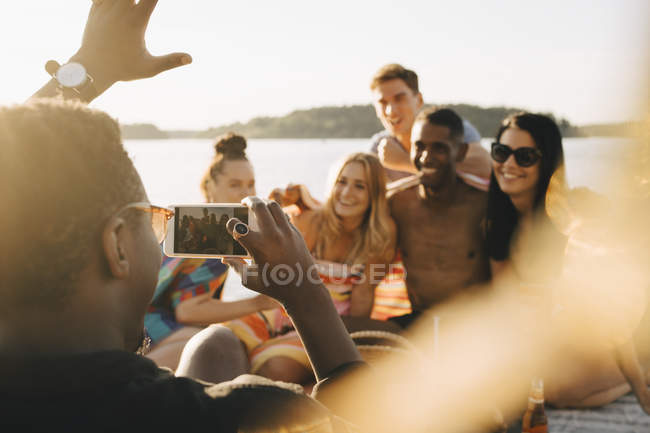 Man photographing cheerful friends on mobile phone at jetty during summer — Stock Photo