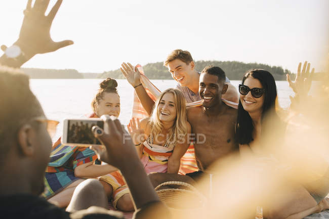 Man photographing happy friends on smart phone at jetty in summer — Stock Photo