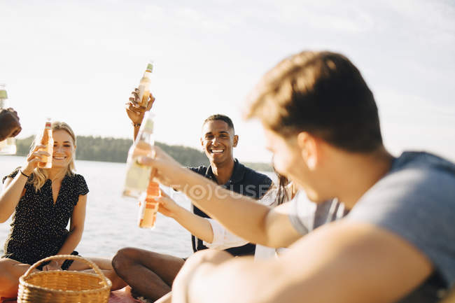 Friends enjoying drinks while sitting on jetty against sky in summer — Stock Photo