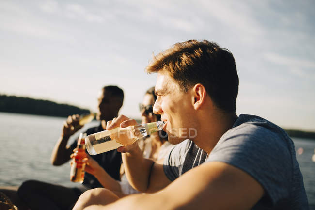 Man enjoying drink with friends while sitting on jetty against sky in summer — Stock Photo