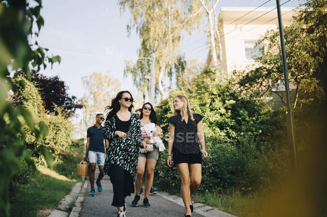 Freundinnen gehen auf Fußweg inmitten von Bäumen — Stockfoto