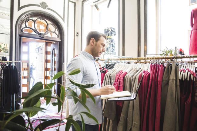 Vista lateral do balconista olhando para o rack de roupas enquanto segura livro e laptop na boutique — Fotografia de Stock