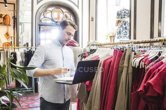 Confident male entrepreneur using laptop while standing by clothes rack in boutique — стокове фото