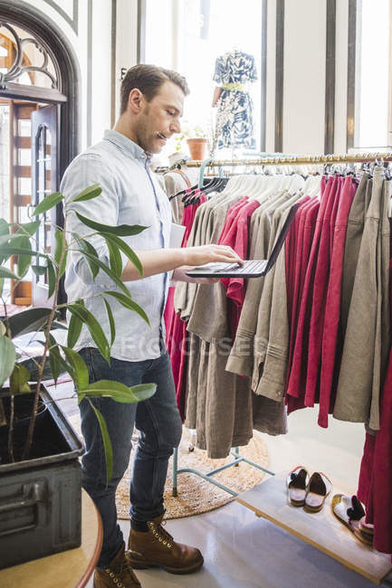 Full length of owner using laptop while standing by clothes rack in store — стокове фото