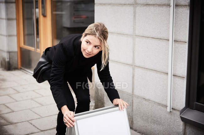 Female real estate agent looking away while arranging blank signboard on sidewalk — Stock Photo