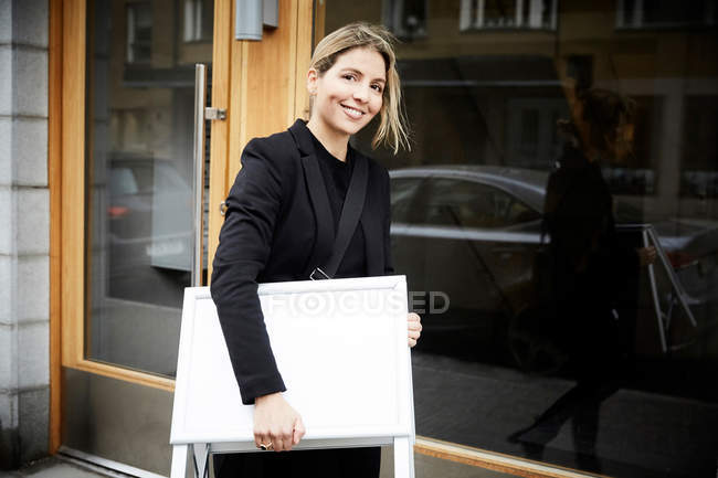 Portrait of smiling female real estate agent with blank signboard in city — Foto stock
