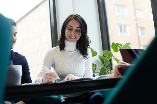 Smiling woman with man signing property papers at real estate office — Stock Photo