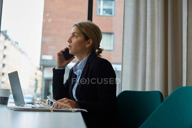 Confident real estate agent talking on smart phone in office — Stock Photo