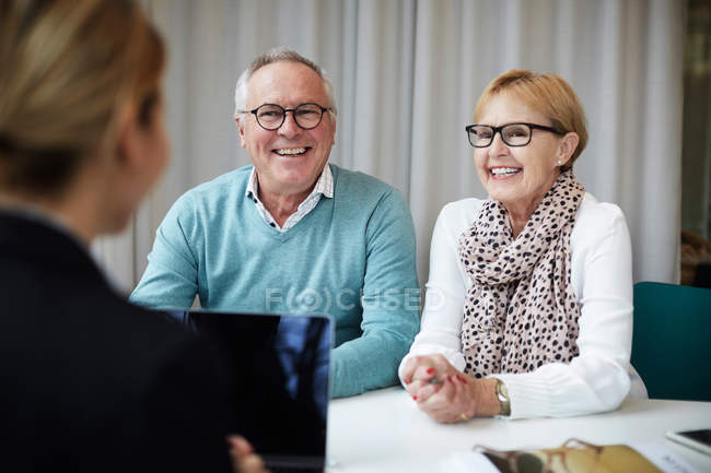 Smiling retired couple talking with female agent in real estate office — Stock Photo