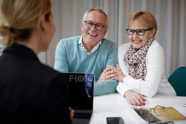 Happy senior couple talking to real estate agent in office — Stock Photo