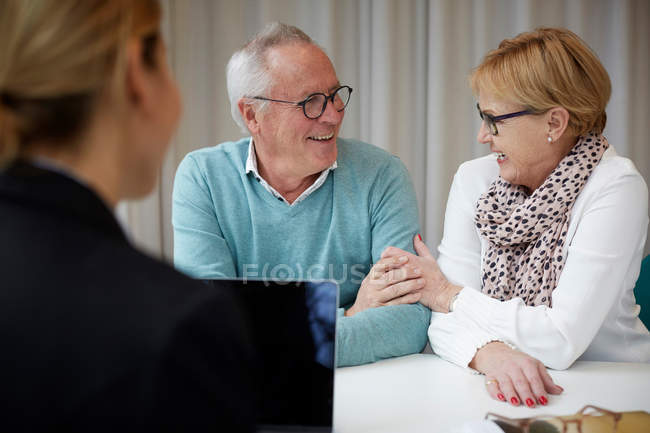 Smiling retired couple with female agent in real estate office — Stock Photo