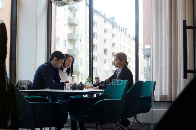 Real estate agent discussing with couple in office — Stock Photo
