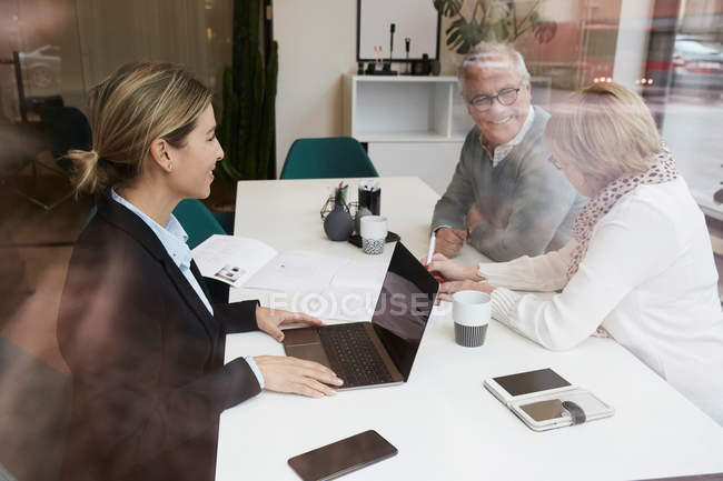Female estate agent discussing with senior couple over property documents in office — Stock Photo