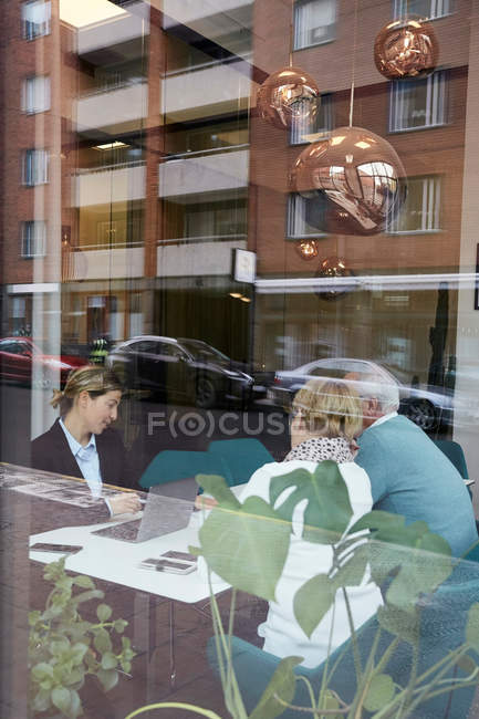 Real estate agent talking to senior man and woman in office — Stock Photo
