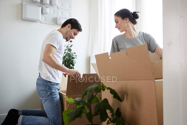 Couple unpacking cardboard boxes in new house — Stock Photo