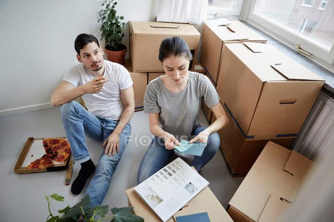 Couples pensifs avec la pizza et les échantillons de couleur pendant la nouvelle relocalisation à la maison — Photo de stock