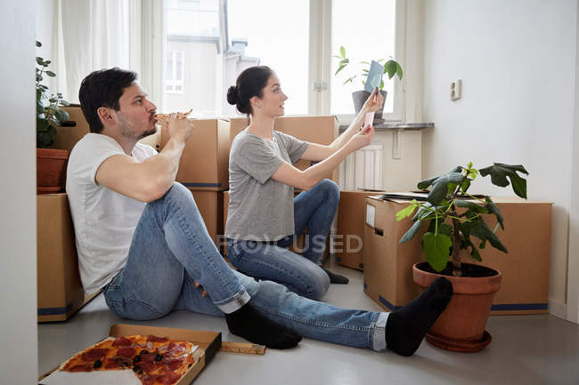 Man eating pizza while looking at woman choosing color swatches in new house — Stockfoto