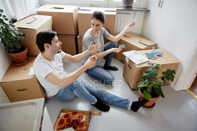 Couple discussing over color swatches while having pizza at new home — Stock Photo