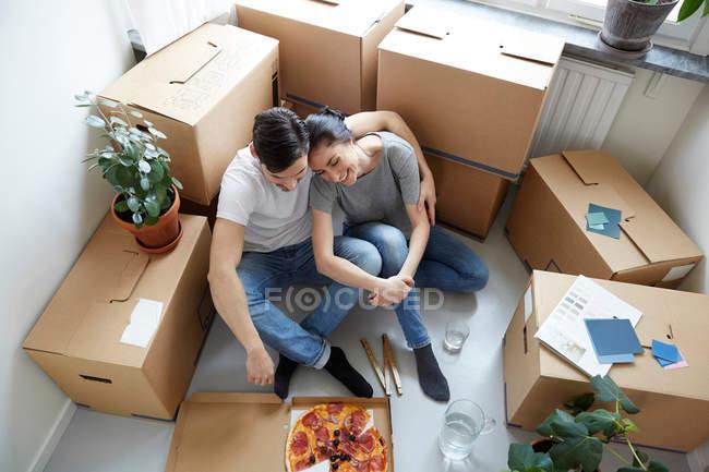 Vue grand angle du couple se reposant ensemble tout en ayant la pizza pendant le déménagement de la maison neuve — Photo de stock