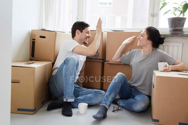 Couples heureux donnant le haut-cinq pendant la coupure de café tout en déménageant dans la nouvelle maison — Photo de stock