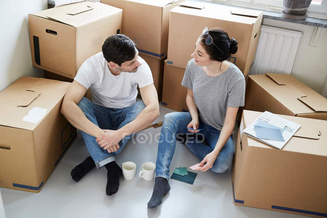 High angle view of couple discussing over color samples during coffee break while moving in new house — Stock Photo