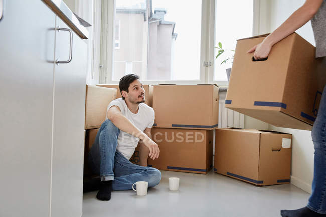 Man with coffee mugs looking at woman carrying cardboard boxes in new house — Stock Photo