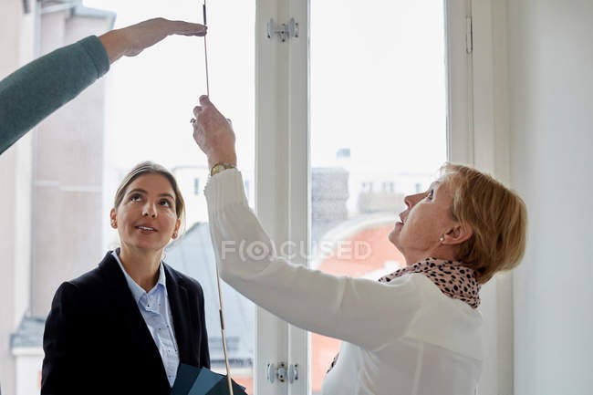 Real estate agent looking at senior couple taking measurements in new house — Stock Photo