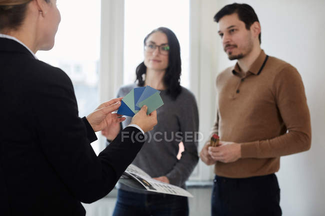 Female estate agent showing color samples to couple in new house — Stock Photo