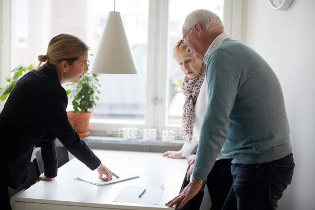 Realtor explaining documents of new house to senior couple — Stock Photo