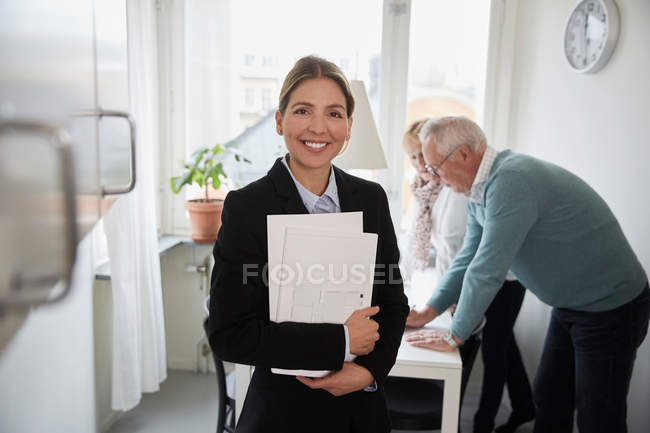 Portrait of smiling real estate agent holding documents with senior couple in background — Stock Photo