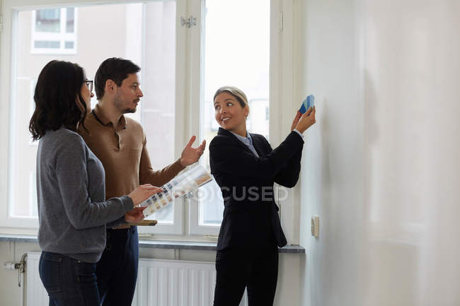 Real estate agent showing color samples to couple in new home — Stock Photo