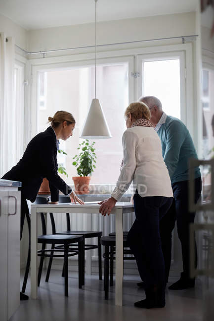 Full length of estate agent explaining documents of new house to senior couple — Stock Photo