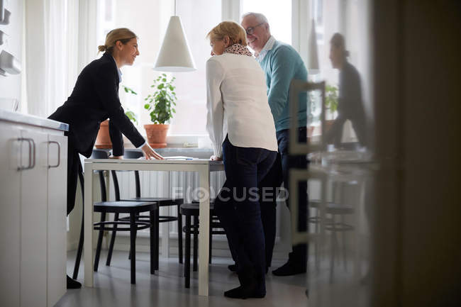 Smiling estate agent and senior couple discussing over documents of new house — Stock Photo