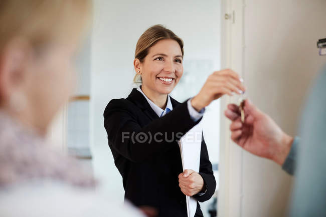 Confident smiling realtor giving house keys to couple — Stock Photo