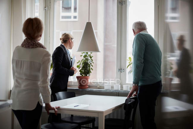 Senior couple and real estate agent looking through window at new home — Stock Photo