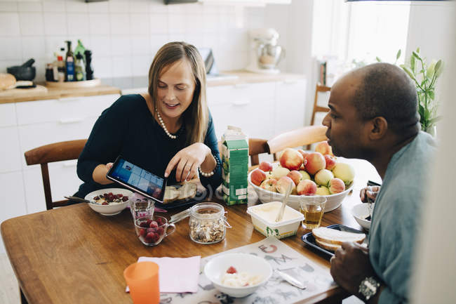 Woman showing digital tablet to man while having breakfast on dining table at home — Stockfoto