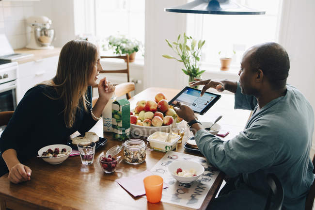 Man showing digital tablet to woman while having breakfast on dining table at home — Stockfoto