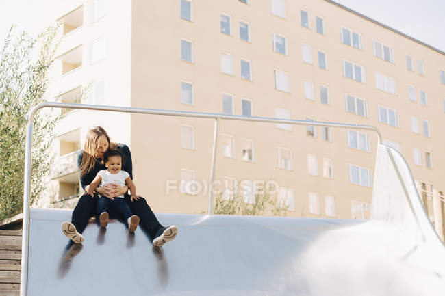 Mother playing with daughter on slide at park in city — Fotografia de Stock