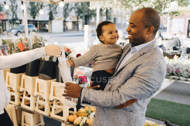 Smiling man with daughter buying food from owner in market — Stock Photo