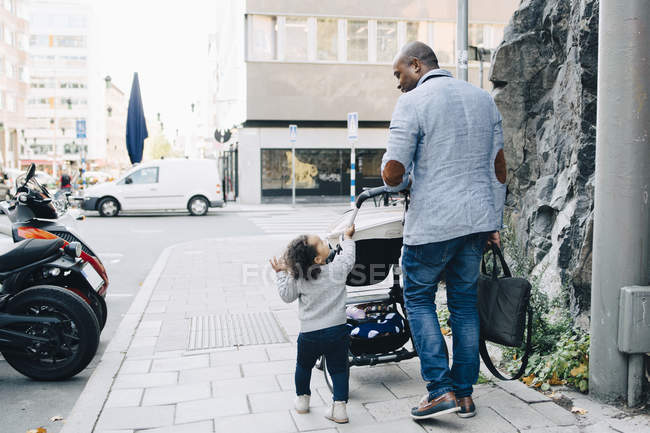 Full length of father talking to daughter while walking with carriage on sidewalk in city — Stock Photo