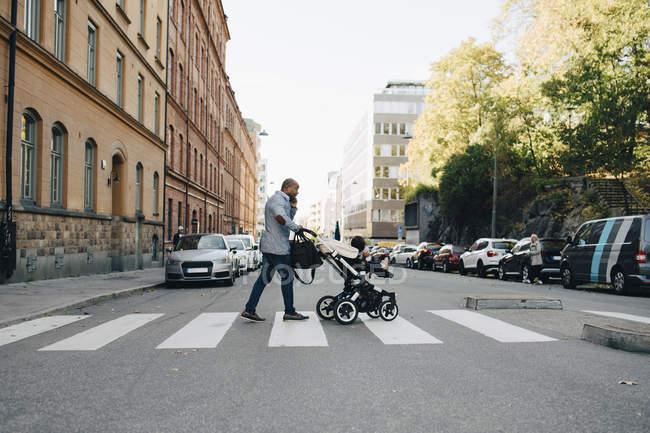 Повна довжина батька, що розмовляє по мобільному телефону, штовхаючи дочку в кареті на міській вулиці — стокове фото
